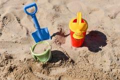 Bunte Sommerstrandspielwaren, -eimer, -berieselungsanlage und -schaufel auf Sand Stockbild