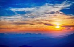 Bunte Sonnenuntergangsonnenscheinwolken und über Blau Stockfoto