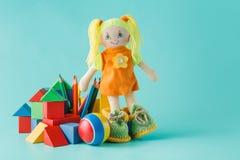 Bunte Spielwaren-Sammlung mit Puppe auf Aquamarin stockfoto