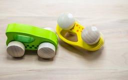 2 bunte Spielzeugautos, mit einem umgekippt, auf einem Holztisch Lizenzfreies Stockfoto