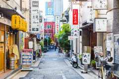 Bunte städtische ruhige Straße in Japan mit verschiedener Shopgeschäfts-Straßenschildfahne in der Stadt Lizenzfreie Stockfotos