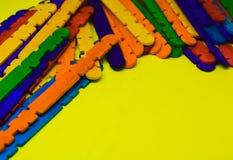 Bunte Stöcke mit gelbem Hintergrund stockbild