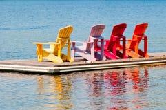Bunte Stühle auf einem Dock Lizenzfreie Stockfotos