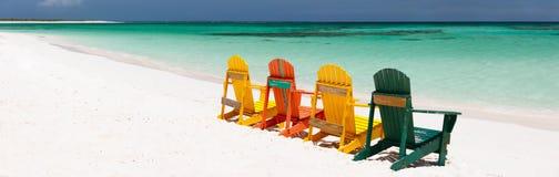 Bunte Stühle auf karibischem Strand Stockbild