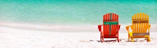 Bunte Stühle auf karibischem Strand Stockfoto