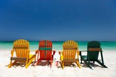 Bunte Stühle auf karibischem Strand Stockfotografie