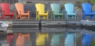 Bunte Stühle in Folge auf dem Dock am See im Sommer Stockfotografie