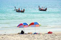 Bunte Stühle und Regenschirm auf Strand Lizenzfreies Stockbild