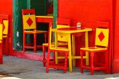 Bunte Stühle und Tabellen Stockfotos