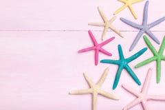 Bunte Starfish auf rosa hölzernem Hintergrund lizenzfreies stockfoto