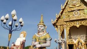 Bunte Statuen nahe asiatischem Tempel Dekorativer buddhistischer Tempel am sonnigen Tag im orientalischen Land Hotei-Statue drauß stock footage