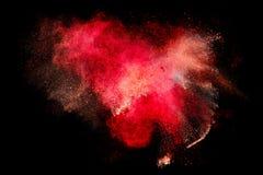 Bunte Staub-Partikel-Explosion lokalisiert auf schwarzem Hintergrund Stockbilder
