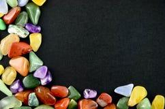 Bunte Steine der Nahaufnahme auf schwarzem Hintergrund Stockfotos