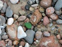Bunte Steine und grünes Glas Lizenzfreies Stockbild