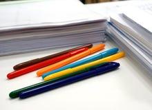 Bunte Stifte und documets auf dem Tisch Lizenzfreie Stockfotografie