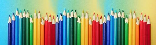 Bunte Stifte vereinbarten in den Farben des Regenbogens auf buntem Papier im Verlauf des Regenbogens stockfoto