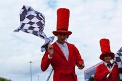 Bunte stiltwalkers in rote Kostüme stockbild