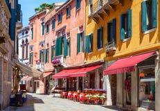 Bunte Straße mit Tabellen des Cafés an einem sonnigen Morgen, Venedig, Italien Stockfotografie