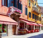 Bunte Straße mit Tabellen des Cafés an einem sonnigen Morgen, Venedig, Italien Lizenzfreie Stockbilder