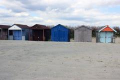 Bunte Strandhütten auf einem englischen Strand Stockfotografie