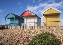 Bunte Strandhütten auf einem Schindelstrand Lizenzfreies Stockfoto