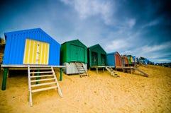 Bunte Strandhütten mit drastischem Himmel Lizenzfreies Stockfoto