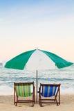 Bunte Strandstühle und -regenschirm auf dem Strand Stockfotos