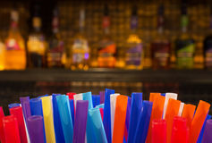 Bunte Strohe und unscharfe Flaschen Geist und Alkohol in der Stange Lizenzfreies Stockbild