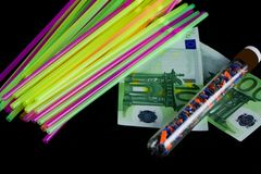 Bunte Strohe, zerquetschter aufbereiteter Plastik in einem Reagenzglas und 100 Eurobanknoten Stockfotografie