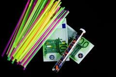 Bunte Strohe, zerquetschter aufbereiteter Plastik in einem Reagenzglas und 100 Eurobanknoten Stockbild