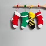 Bunte Strumpfweihnachtssocken auf grauem Hintergrund helles Weihnachtsdesign-Dekorationselement rotes, gelbes, grünes Hängen Stockbild