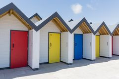 Bunte Türen von Blauem, von Gelbem und von Rotem, wenn jedes einzeln, von den weißen Strandhäusern nummeriert ist, an einem sonni Stockfoto