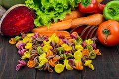 Bunte Teigwaren auf einem dunklen rustikalen Holztisch mit Frischgemüseroten rüben, Grüns, Karotten, Tomaten, Pfeffer Stockfotografie