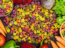 Bunte Teigwaren auf einer Tabelle mit Frischgemüseroten rüben, Grüns, Karotten, Tomaten, Pfeffer Lizenzfreie Stockfotografie