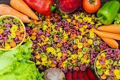 Bunte Teigwaren auf einer Tabelle mit Frischgemüseroten rüben, Grüns, Karotten, Tomaten, Pfeffer Gesundes Nahrungsmittelkonzept Stockfotos