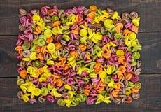 Bunte Teigwaren gefärbt durch Gemüserote rüben, Grüns, Spinat, Karotten, Tomaten, Pfeffer auf einem dunklen Holztisch Gesundes Le Lizenzfreie Stockbilder