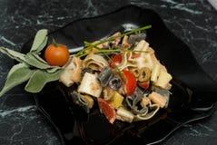Bunte Teigwaren mit Soße, olivevs, Tomaten im Schwarzblech Beschneidungspfad eingeschlossen Nahrung Herz-förmiges Macarons auf sc Lizenzfreie Stockbilder