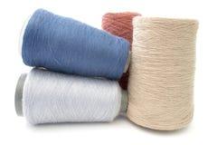 Bunte Threads und Garne auf einem weißen Hintergrund Stockfotos