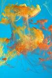 Bunte Tinte in der blauen Flüssigkeit Stockfotografie