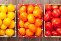 Bunte Tomaten auf Holztisch Stockfotografie