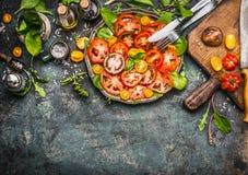 Bunte Tomatensalatvorbereitung mit Schneidebrett, Platte und Tischbesteck, Draufsicht lizenzfreies stockbild