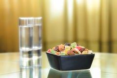 Bunte trockene Früchte in einem kleinen schwarzen Quadrat rollen Lizenzfreie Stockfotografie