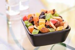 Bunte trockene Früchte in einem kleinen schwarzen Quadrat rollen Stockfoto