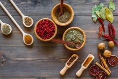 Bunte trockene Kräuter und Gewürze für das Kochen des hölzernen von Draufsicht Küchentischhintergrundes des Lebensmittels lizenzfreie stockfotos