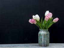 Bunte Tulpen blüht auf schwarzem Bretthintergrundholztisch Draufsicht mit Kopienraum Stockfotos