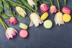 Bunte Tulpen und Makronen auf schwarzem Hintergrund Beschneidungspfad eingeschlossen Lizenzfreies Stockbild