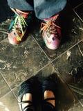 Bunte Turnschuhe und schwarze Schuhe Lizenzfreie Stockfotos