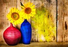 Bunte Vasen mit Sonnenblumen auf einem hölzernen Hintergrund Lizenzfreie Stockbilder