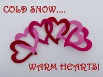 Bunte verbundene Valentinsgrußherzen auf einem Bett des frisch gefallenen Winterschnees mit den kalten grüßenden Schnee-warmen He Stockfotos