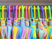 Bunte vibrierende Regenschirme, die am Gestell hängen stockbild